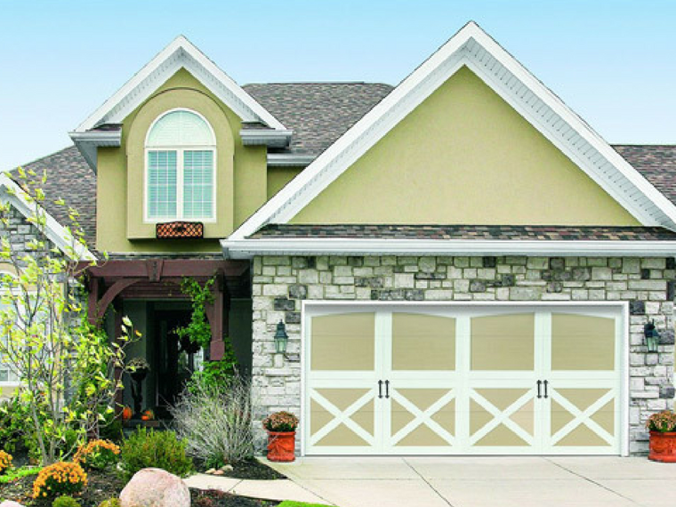 Carriage garage doors with white trim and decorative hardware